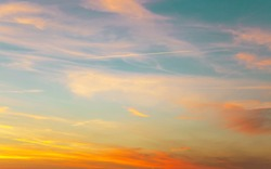 Sunset sky with condensation trail. Texture of bright evening sky during sunset. Dramatic blue and orange, colorful clouds at twilight time. Abstract weather nature background.