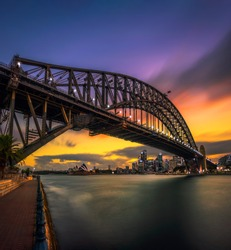 Sunset skyline of Sydney downtown with city lights and Harbour Bridge in Australia. Long exposure.