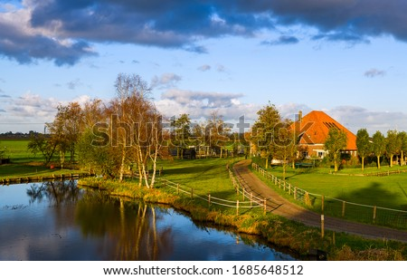Photo of  Sunset spring village river landscape. Farm house river scene. River farm house in spring. Farm house river water reflection