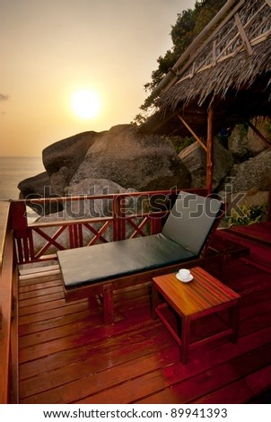 Sunset sunbed on wooden terrace with coffee table