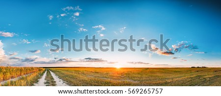 Sunset, Sunrise Over Rural Meadow Field And Country Open Road. Countryside Landscape With Path Way Under Scenic Summer Dramatic Sky In Sunset Dawn Sunrise. Sun Over Skyline Or Horizon.