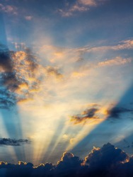 Sunset, the sun behind the clouds with rays of light in the evening during a solar eclipse
