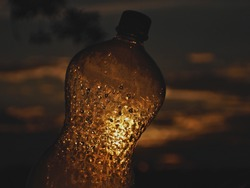 Sunset through abandoned empty plastic bottle in saturated trash can
