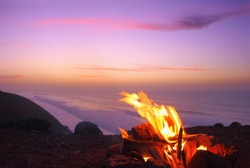 Sunset time in Legzira beach, Sidi Ifni, Morocco, North West Africa. Beautiful nature view, a bonfire is burning on a high shore of Atlantic ocean at the background of colorful evening sky.