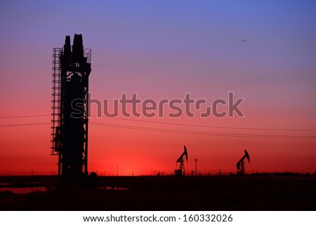 Sunset tower of the pumping unit work in the oil field