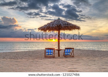 Sunset under parasol on the beach in Thailand