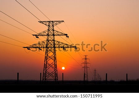 sunset under the high-voltage tower in the background