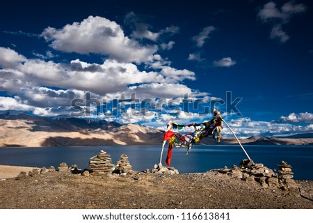 Sunset view at Tso Moriri Lake, Stone pyramid and Buddhist praying flags. Himalaya mountains landscape.India, Ladakh, altitude 4600 m