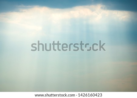 Sunset view of dramatic storm sky with dark clouds and bright sunbeams shining through them. Can be used as nature background #1426160423