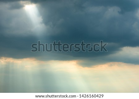 Sunset view of dramatic storm sky with dark clouds and bright sunbeams shining through them. Can be used as nature background #1426160429