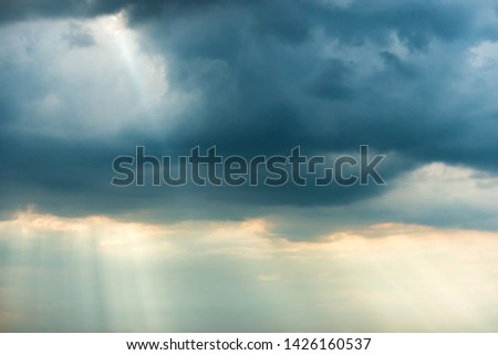 Sunset view of dramatic storm sky with dark clouds and bright sunbeams shining through them. Can be used as nature background #1426160537