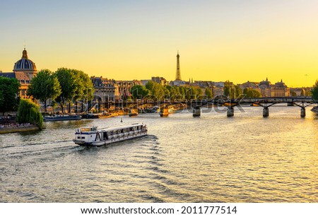 Sunset view of Eiffel tower, Pont des Arts and Seine river in Paris, France. Eiffel Tower is one of the most iconic landmarks of Paris. Architecture and landmarks of Paris.