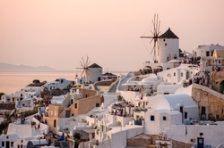 Sunset view of Greek village Oia on Santorini island in Greece. Santorini is iconic travel destination in Greece, famous of its sunsets and traditional white and blue architecture.
