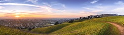 Sunset view of hiking trail on the verdant hills of East San Francisco Bay Area; the city of Hayward and the bay visible in the valley; California