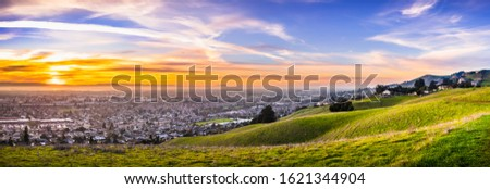 Sunset view of residential and industrial areas in East San Francisco Bay Area; green hills visible in the foreground; Hayward, California Stockfoto ©