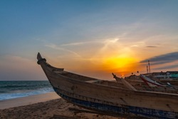 Sunset view of the beach at Cape Coast, Ghana. The ocean and wooden fishing boats on the foreground