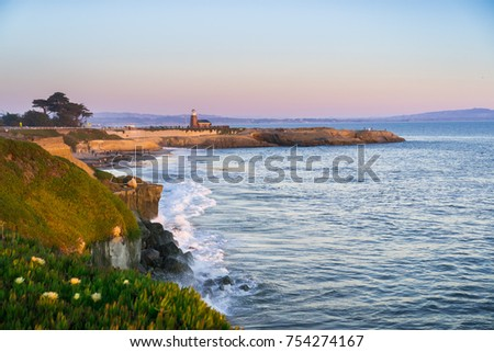 Sunset view of the Pacific Ocean rugged coastline, Santa Cruz, California; Santa Cruz surfing museum in the background #754274167