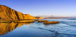 Sunset view of the Pacific Ocean shoreline, with golden colored cliffs reflected on the wet sand, Drakes Beach, Point Reyes National Seashore, California