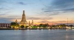 Sunset view of Wat Arun (Temple) across Chao Phraya River in Bangkok, Thailand.