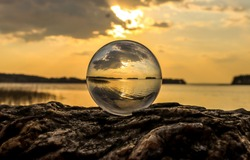 Sunset view over the lake through a glass ball. Transparent sphere on lake at sunset. Lake at sunset in clear sphere. Lake at sunset in glassware ball