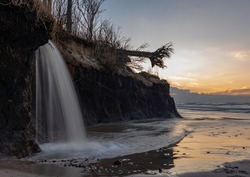 sunset waterfall on the floor by the sea with a beautiful small river estuary in the wide sea waters and clouds on the horizon