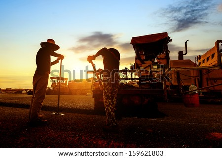 Sunset, when the work of the workers, asphalt road under repair.
