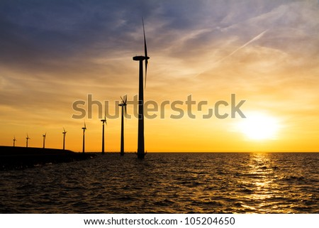 Sunset wind turbines in a row