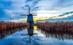 Sunset windmill river water landscape. Windmill silhouette sunset river water