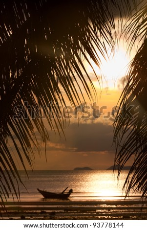 Sunset with boat in the sea and palm tree leaves