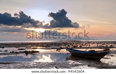 Sunset with boat in the sea, cloudy sky and low water