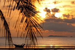 Sunset with boat in the sea, defocused palm tree