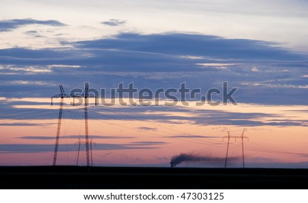 Sunset with  colorful clouds and electricity pylons with smoke in background