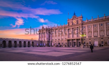 Sunset with dramatic pink sky and clouds behind the front facade of the Royal Palace from the Plaza de Armeria or Armory square in front of the Almudena cathedral in the sunlight at blue hour, dawn