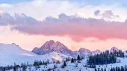 Sunset with dramatic sky and snowy mountain peaks illuminated by sunlight, Tatra Mountains in winter time. Mountain range in Bialka Tatrzanska, Poland
