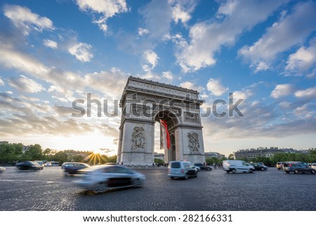 Sunset with dramatic sky behind Arc de Triomphe and blurred cars traffic along the Champs-Elysees