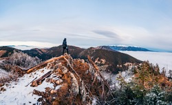 Sunset with inversion. Hiker, who is watching this breathtaking beautiful scenery. Travel destination. Tatry in the background. Winter inversion clouds
