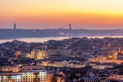 Sunset with orange tones from the Monte Agudo viewpoint in Lisbon, capital of Portugal. In the background the 25th of April Bridge and The Christ the King statue, symbols of the city