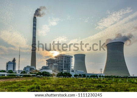 Sunset with power plant and big chimney.