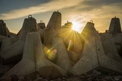 sunset with sunbeams on the background of large boulders on the sea pier