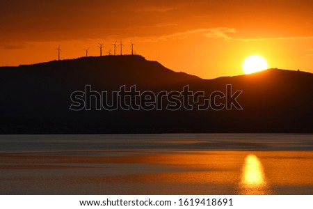 Sunset with windmills over a mountain over the sea