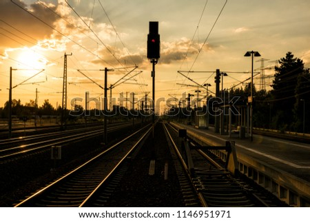 Sunset wraps German railway line with various tracks and catenary in orange light. The red signal indicates stop.