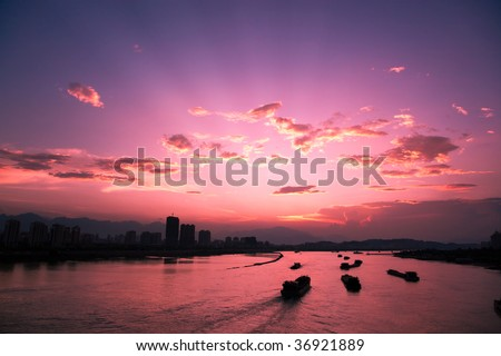 Sunsets with colorful clouds and sailing boats on the river in China #36921889