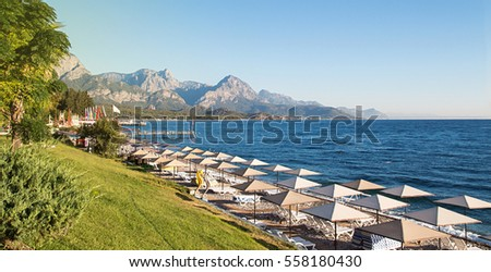 Sunshades and chaise lounges on beach. Turkey, Kemer. Beautiful view of mountains and sea from embankment Stok fotoğraf ©