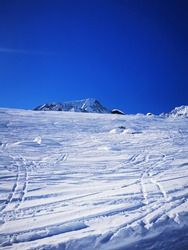 Sunshine and sunny views on snow-capped pristine white mountains in Swiss Alps off pist eof Arolla ski resort