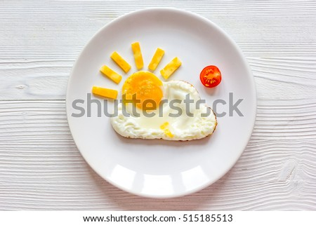sunshine fried eggs breakfast for kid on wooden background