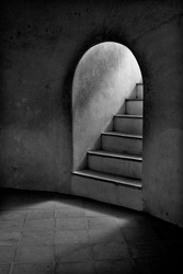 Sunshine light through the curved door in dark room old castle concrete wall with stairway up to rooftop, vintage black and white photo.