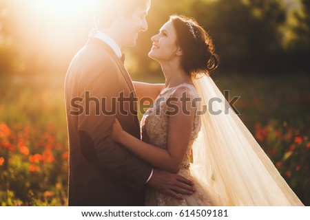 Sunshine portrait of happy bride and groom outdoor in nature location at sunset. Warm summertime #614509181
