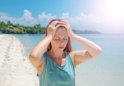 Sunstroke on beach, hot time dy seaside. Bright sun negative impact. Medicine on summer photo. Woman with sun stroke holding head. Tropical vacation threat. Outdoor healthy tip. Tourist with sunstroke