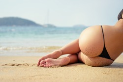 Suntan and vacation. Close up of sexy young woman in bikini laying on sand beach.