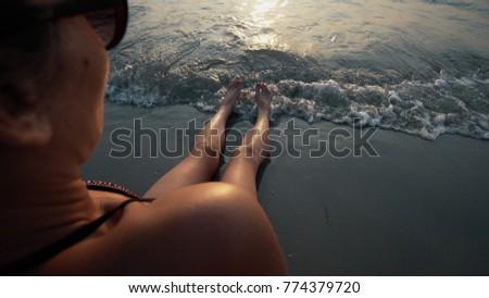 Suntan beach woman tanning sexy legs relaxing swimming in ocean water with sunset sun drawing in sunscreen lotion sunblock cream #774379720